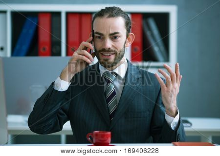 Angry businessman on the phone cursing office