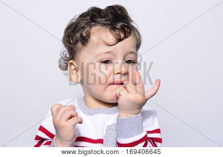 Portrait of a cute baby eating a banana looking not happy.One year old kid eating fruits by himself. Adorable curly hair boy being hungry.