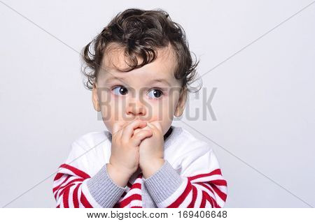 Portrait of a cute baby boy looking up surprised.Adorable one year old child looking away curious with his hands on the mouth. Baby wondering, scared, afraid.