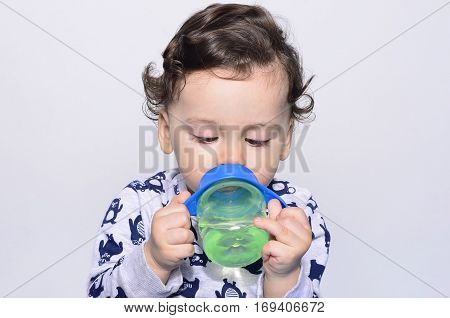 Portrait of a cute toddler drinking water from the bottle. One year old kid looking down funny at the baby cup. Adorable curly hair boy being thirsty.