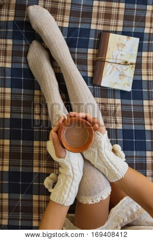 Girl is sitting on a chekered plaid in knee-height socks and in hand warmers, holding a cup with coffee, warming in frosty winter morning in her bed