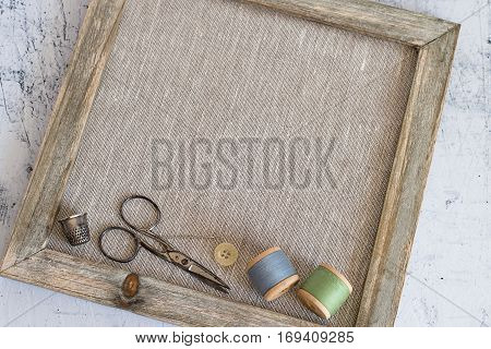 The composition on the theme of needlework. Spools of sewing thread, scissors, needle, button and thimble in an old wooden frame on a light background.