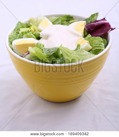 Green Salad with Hard Boiled Egg and Salad Dressing in a Yellow Bowl.