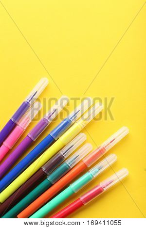 Felt-tip pens on a yellow background, close up