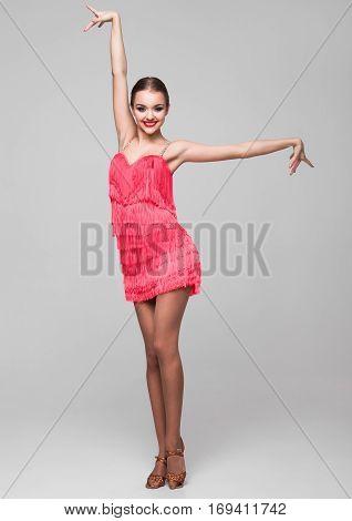 Beautiful ballroom dancer girl in elegant pose red dress on grey background