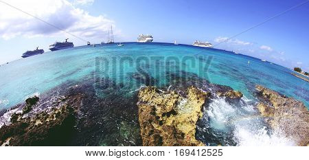 Fish-eye view of rocky shore, green-blue water and cruise ships in Grand Cayman