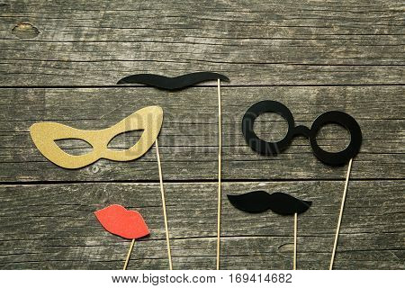 Fake lips, glasses and mustaches on sticks on old wooden background.