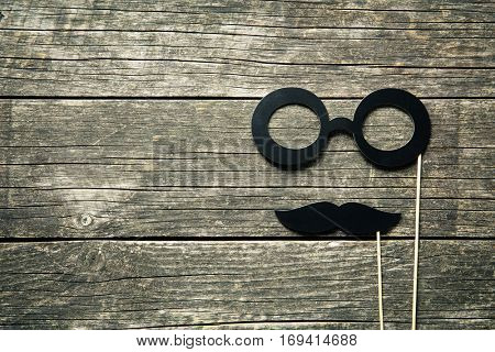 Fake glasses and mustaches on sticks on old wooden background.