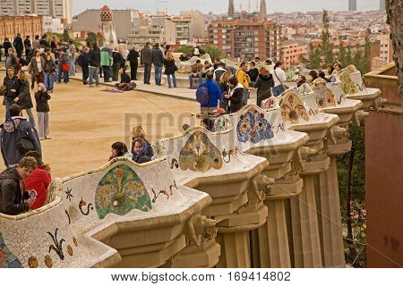 Tourist crowds at the bench on top at Parc Guell with view over Barcelona. Park designed by Antoni Gaudi. December 2008.