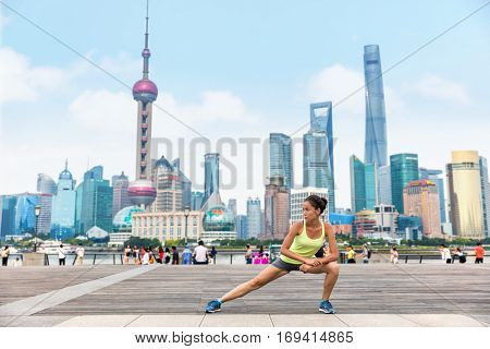 Runner stretching after workout on famous boardwalk with skyline in Shanghai, China. Urban city lifestyle. Active Asian woman training outside on the Bund doing leg exercises muscle stretches.