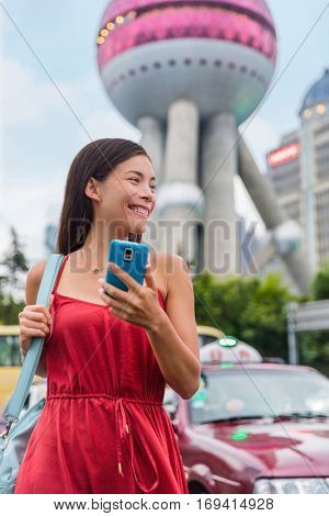 Asian woman chinese lady taking a taxi cab ride paying her fare using an online mobile pay payment app via smartphone. Businesswoman in business center financial district in Pudong, Shanghai, China.