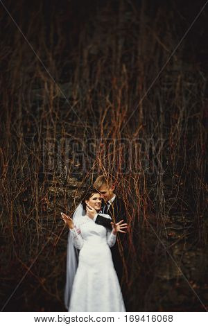 Bride Smiles Standing Behind A Dry Ivy With A Fiance