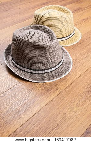 Two Men's Straw Hats on Wood Flooring