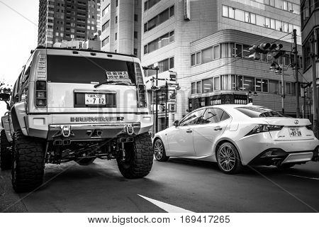 TOKYO, JAPAN - NOVEMBER 12, 2016: Luxury cars on the street of Ikebukuro district of Tokyo, Japan. Tokyo Metropolis is both the capital and most populous city of Japan.