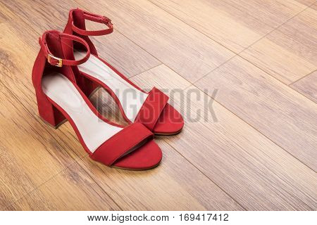Women's Red Suede Sandals on Wood Flooring