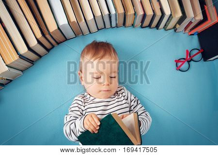 One year old baby among books with spectackles. Serious child reading