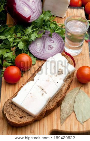 Lard on bread tomatoes onions fresh herbs and vodka on the table