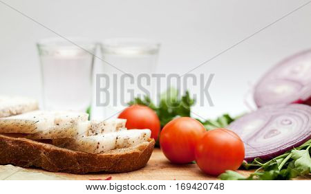 Lard on bread tomatoes onions fresh herbs and vodka on a white background