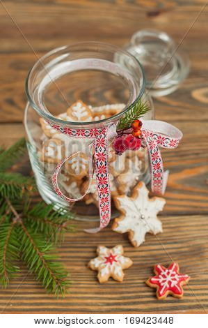 Glass jar with gingerbread cookies on wooden table.