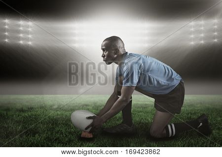 Confident rugby player looking away while keeping ball on kicking tee against spotlight 3d