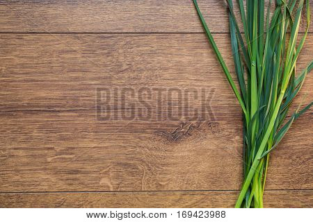A bunch of fresh spring green grass on a wooden background. An old wooden texture with terrestrial plants. Land plants. Plant with green stems and low The components for the preparation of salad. Vegetarian food