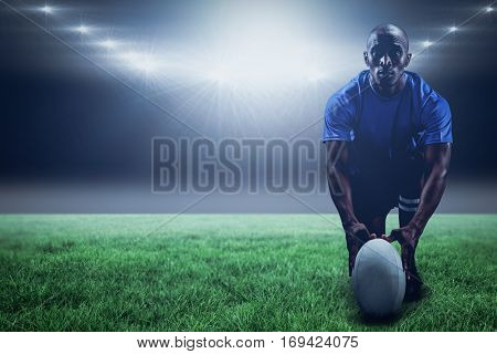 Portrait of rugby player holding ball while kneeling against spotlight and copy space 3d