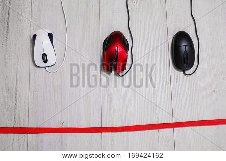 White and black and red computer mouse on a white wooden background. Competition in the business red tape.