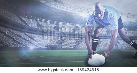 Portrait of sportsman bending and holding ball while playing rugby against rugby stadium with copy space 3d