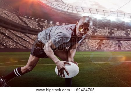 Determined sportsman looking away while playing rugby against rugby stadium with copy space 3d