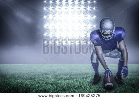 American football player holding ball while crouching against spotlight with copy space 3d