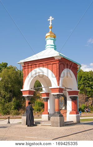 priest baptized in front of the chapel. Chapel of All Who Sorrow joy. Russia Karelia Valaam Island.