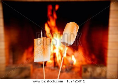 Two big marshmallows on sticks being roasted by the fire