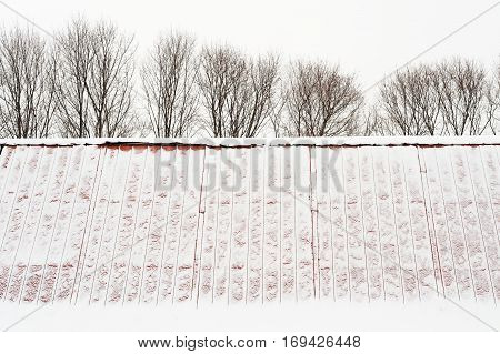 Snow covered gable roof and leafless trees in winter