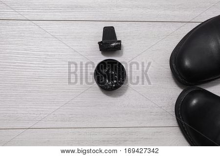 Black leather shoes on a wooden white background. Cream and sponge for shoes. Formal business men leather shoes shining