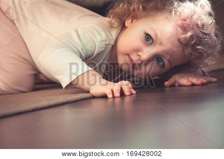 Curious cute child hiding under the bed in kids room and looking scared