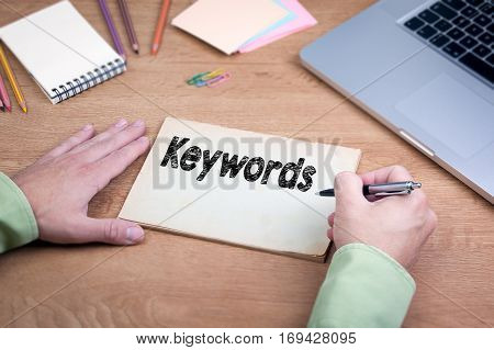 Hand writing Keywords. Office desk with a laptop and stationery.