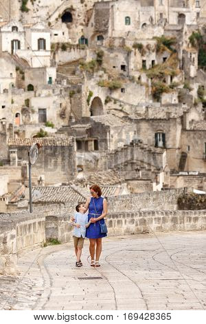 Young mother and her little son walking outdoors in italian city