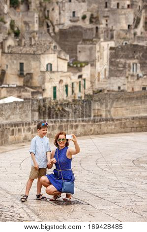 Young mother with her little son walking outdoors in italian city and making selfie