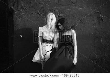 red-haired girl in a red dress and girl with long white hair in a white dress the two girls standing near a red wall the wind picks up the dress and her hair paint was spilled on the dress