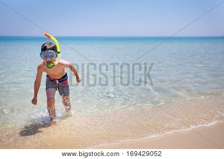 Vacation boy happy snorkeling running having fun in water splashing during summer holiday vacation