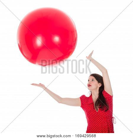Beautiful woman in red dress catching a big red balloon above her head isolated on a white background