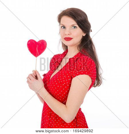 Beautiful woman in red dress holding red heart-shaped lollipop in front of her isolated on white