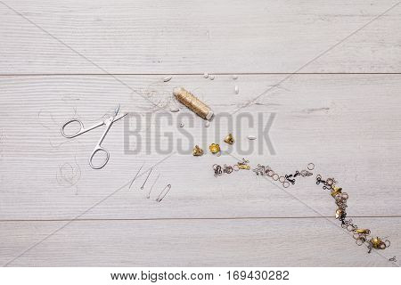 Reel gold thread on a wooden table. Pearls needles scissors hooks for needlework. Accessories. Tools seamstress. The creative process