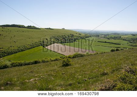 Chalk downland landscape with grassland hills and farmed fields in central valley