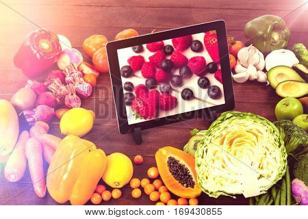 Digital tablet surrounded with fresh fruits and vegetable against high angle view of fruits