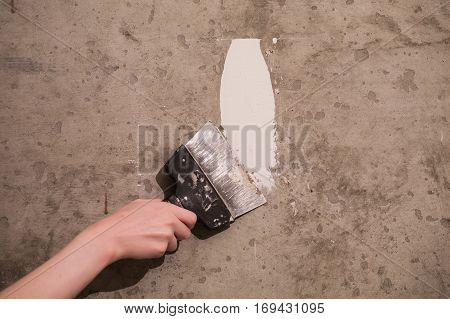 Tools dirty spatula in hand on a concrete background work plasterer painter .Remont. Trowel in hand of man. Plastered walls. Space for text
