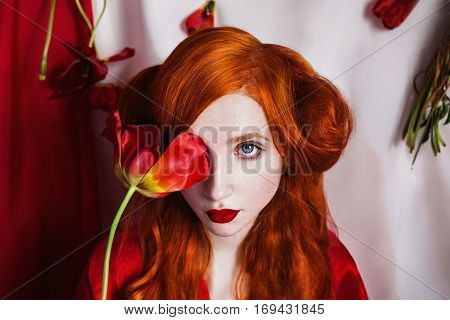 Red-haired girl with blue eyes and pale skin in a red coat. Woman with flower in hand with red lips closes eyes red tulip. Curling hair. Gothic style on a white background.