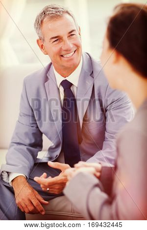 Smiling businessman talking to his workmate in bright office