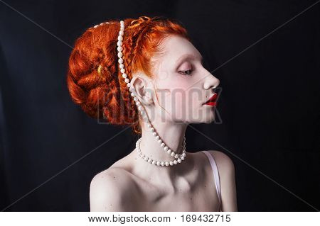 Red-haired girl with a high coiffure with white beads on the head. A woman with pale skin with moles with red lips on a black background. Omitted look. Beautiful profile.