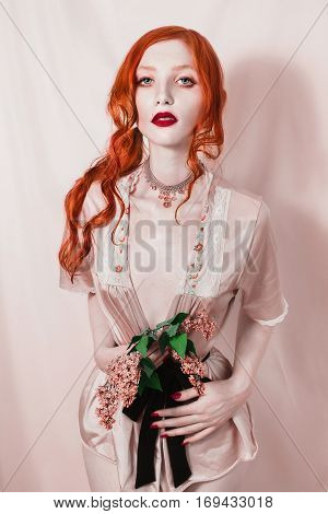 Red-haired girl with pale skin and big eyes looking at the camera. Red curly hair. A woman in a white gown with a bouquet of lilac in the hands on a pink background. Beautiful slim model.